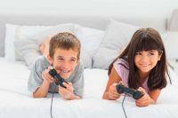 Imagen de niños jugando a videojuegos tumbados en la cama.